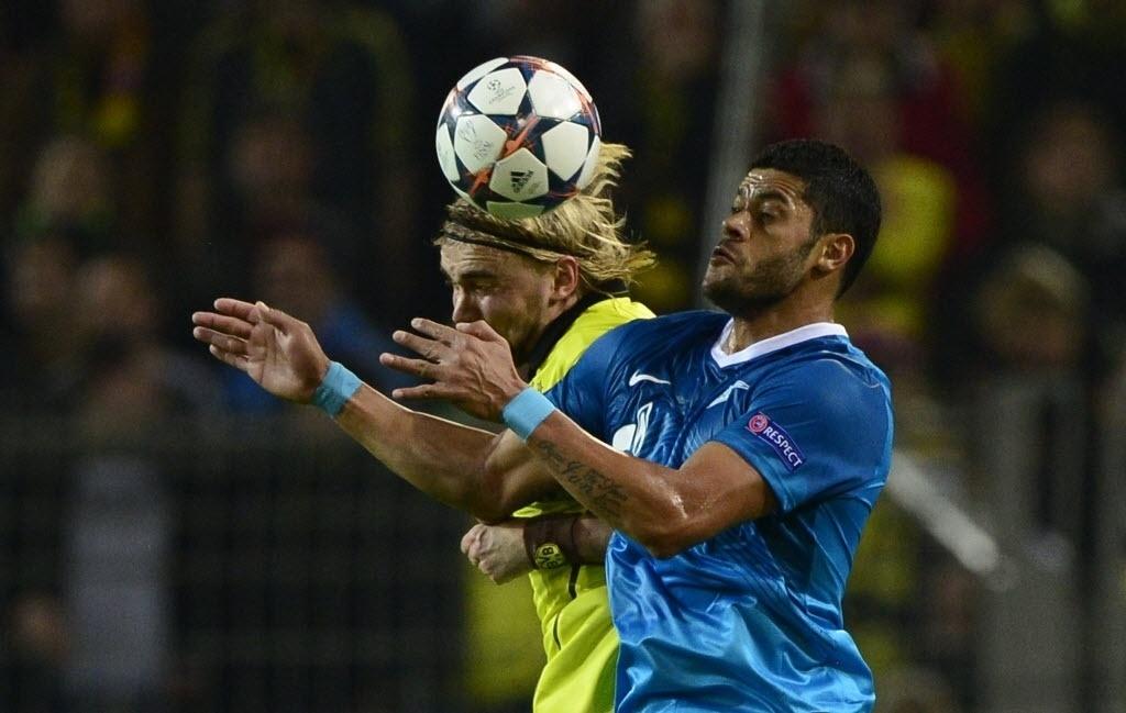 19.mar.2014 - Hulk disputa bola aérea com Marcel Schmelzer, do Borussia Dortmund em duelo válido pelas oitavas de final da Liga dos Campeões