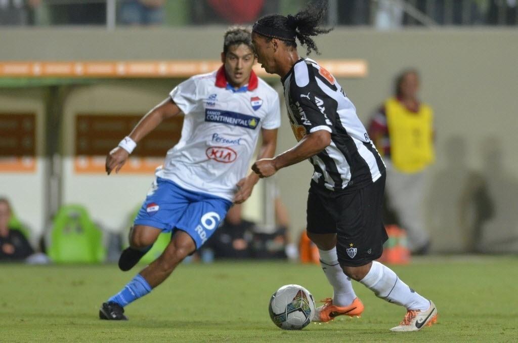 19.mar.2014 - Ronaldinho Gaúcho dribla Silvio Torales, do Nacional, durante jogo válido pela fase de grupos da Libertadores