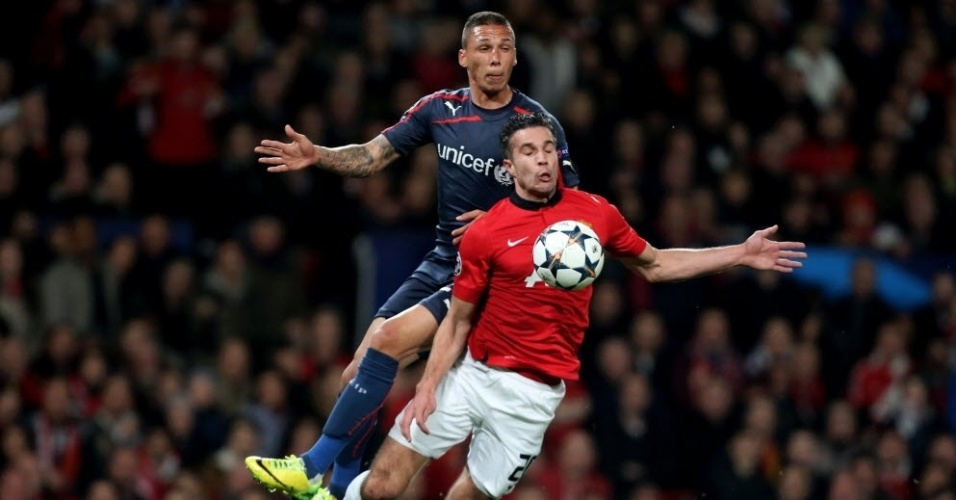 19.mar.2014 - Van Persie tromba com Jose Holebas, do Olympiakos, em lance que rendeu pênalti para o Manchester United
