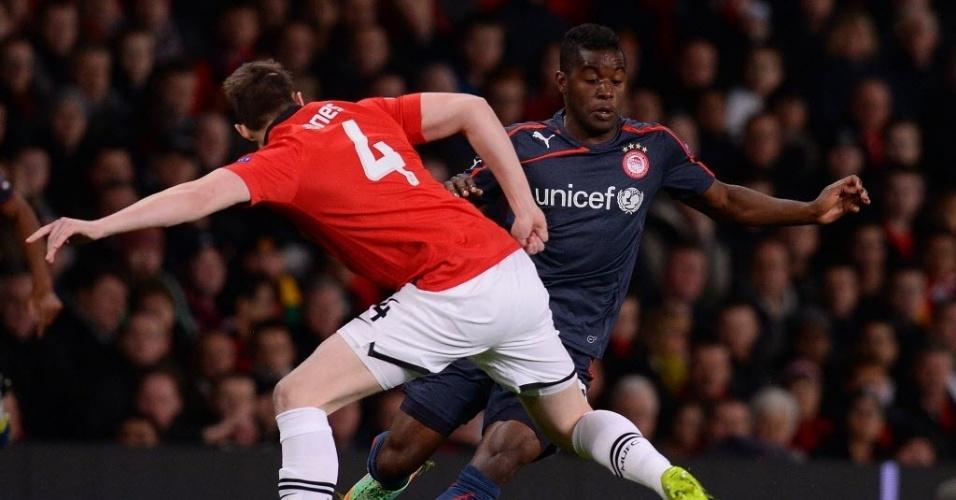 19.mar.2014 - Zagueiro do Manchester United Phil Jones tenta desarmar Joel Campbell, do Olympiakos, durante jogo de volta das oitavas de final da Liga dos Campeões
