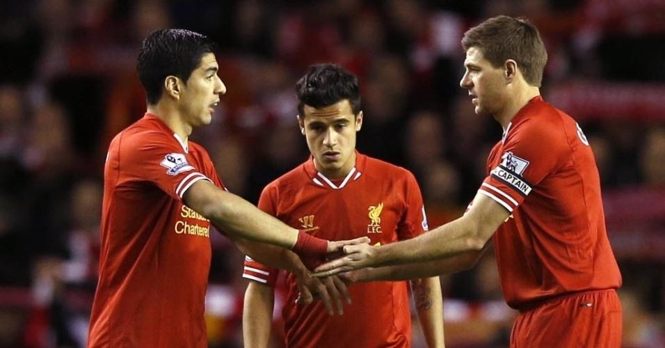 26.mar.2014 - Observados pelo brasileiro Philippe Coutinho, Luis Suárez cumprimenta Gerrard antes da partida entre Liverpool e Sunderlan pelo Campeonato Inglês