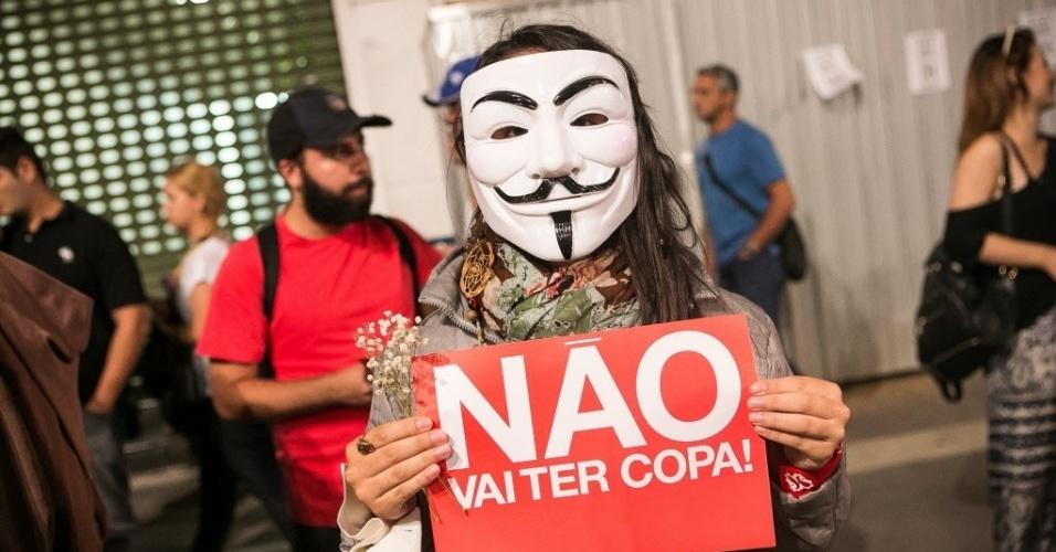 """27.03.14 - Usando máscara, manifestante exibe cartaz com a frase """"não vai ter Copa"""", nome do movimento contra o Mundial no Brasil"""
