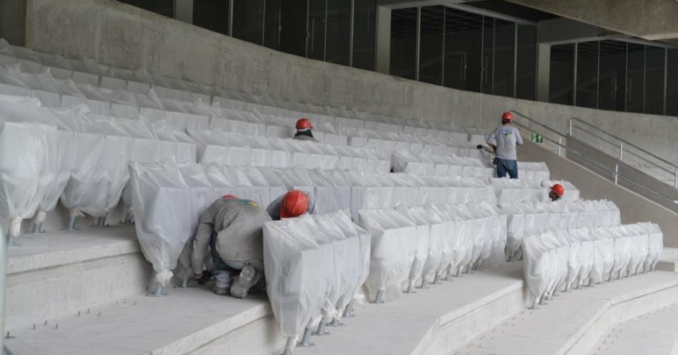27.mar.2014 - Funcionários instalam assentos na nova Arena da Baixada