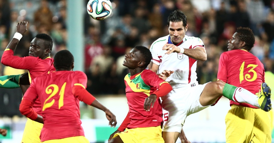 5.mar.2014 - Amir Hossein Sadeghi, do Irã, tenta se virar sozinho no meio da defesa de Guiné durante amistoso entre as duas seleções em Teerã; mesmo jogando em casa, iranianos perderam por 2 a 1