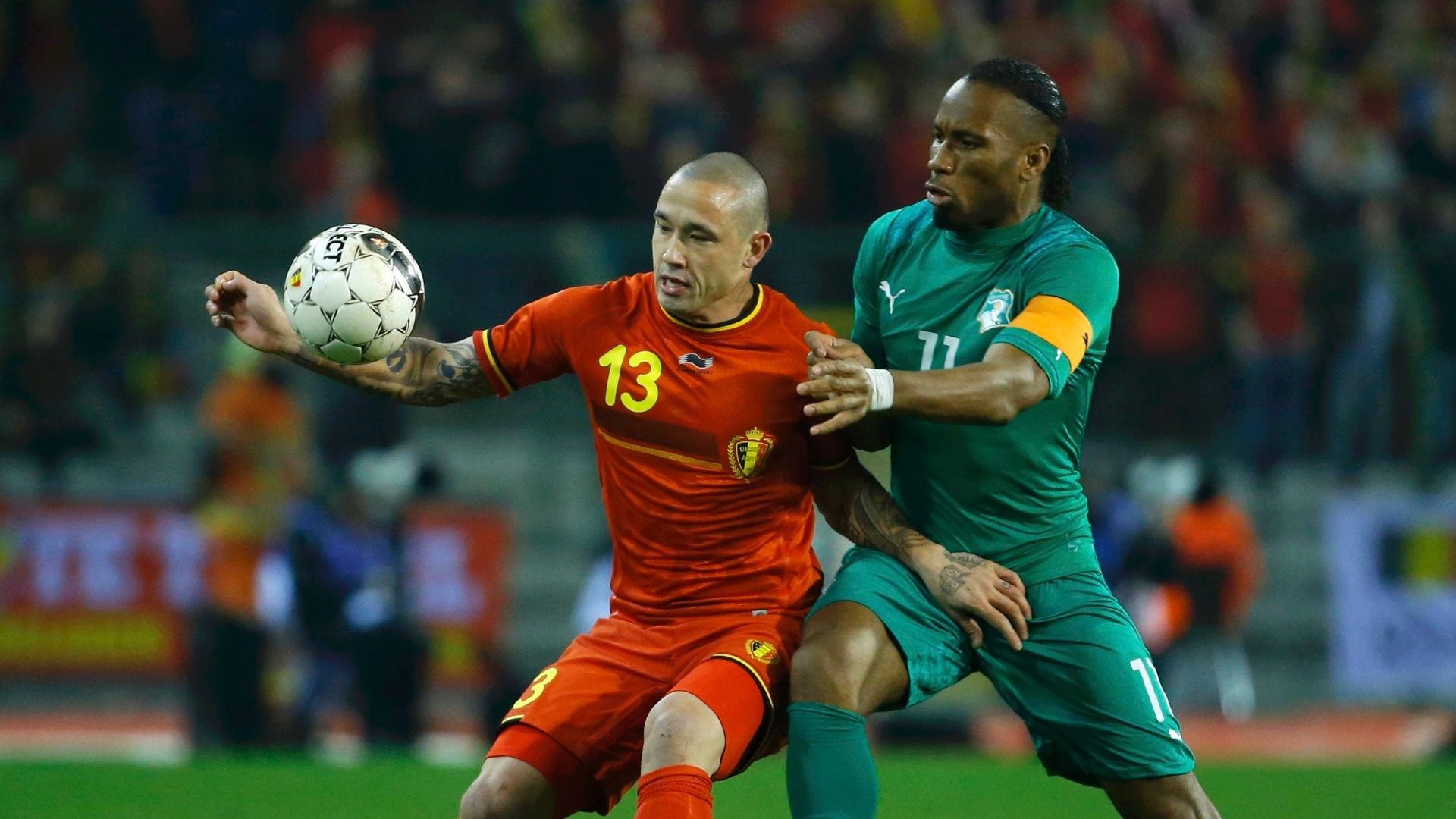 5.mar.2014 - Didier Drogba (d), da Costa do Marfim, tenta se livrar da marcação do belga Radja Nainggolan durante o empate por 2 a 2 entre as duas seleções, em amistoso disputado em Bruxelas