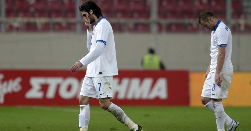 5.mar.2014 - Georgios Samaras (e) e Avraam Papadopoulos deixam o campo cabisbaixos após a derrota por 2 a 0 da Grécia para a Coreia do Sul em amistoso disputado em Pireus (Grécia)