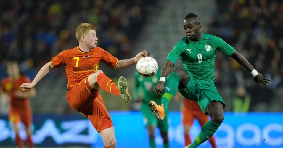 5.mar.2014 - Kevin De Bruyne (e), da Bélgica, disputa jogada com o marfinense Cheikh Tioté durante o empate por 2 a 2 em amistoso disputado em Bruxelas