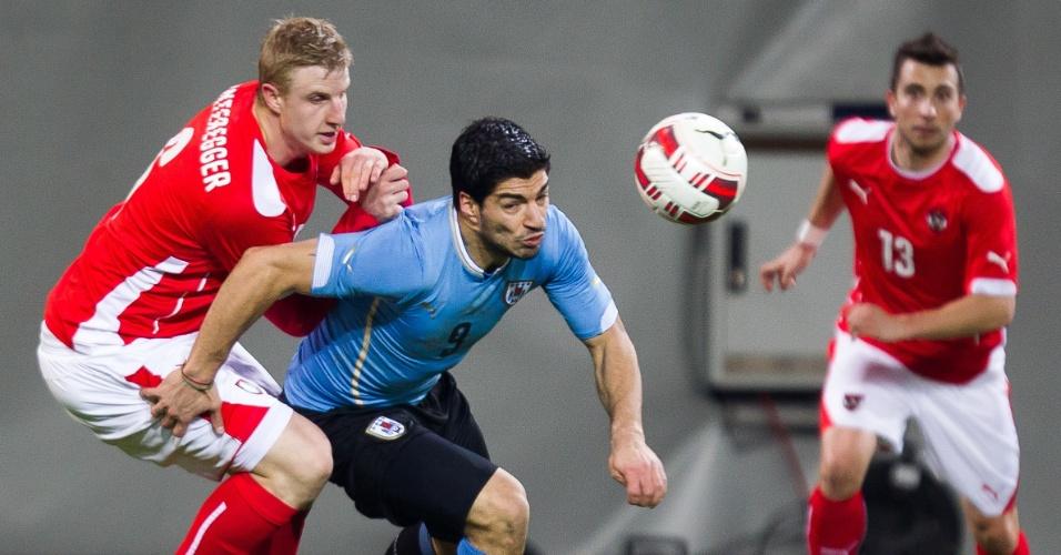 5.mar.2014 - Luis Suárez (c), do Uruguai, tenta se livrar da marcação do austríaco Martin Hinteregger durante o empate por 1 a 1 entre as duas seleções no amistoso disputado em Klagenfurt (Áustria)