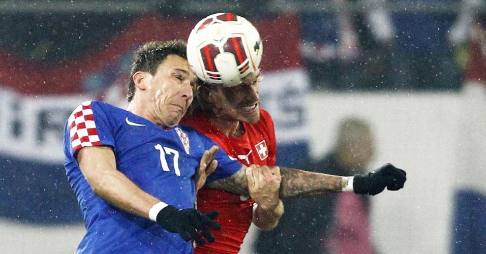 5.mar.2014 - Mario Mandzukic (e), da Croácia, disputa jogada com o suíço Michael Lang durante o empate por 2 a2 entre as duas seleções, em amistoso disputado em St. Gallen (Suíça)