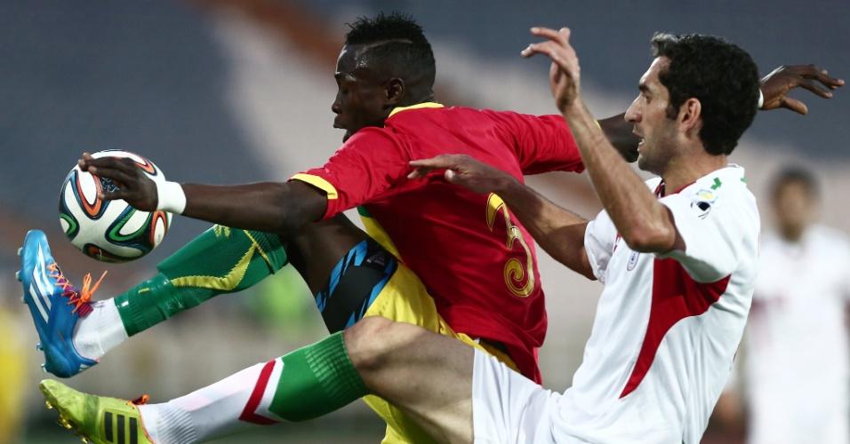 5.mar.2014 - Mojtaba Jabari (d), do Irã, disputa jogada com Issiaga Sylla, de Guiné, durante amistoso em Teerã; mesmo jogando em casa, iranianos perderam por 2 a 1