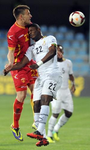 5.mar.2014 - Wakasu Mubarak (d), de Gana, disputa jogada pelo alto com o montenegrino Filip Kasalica durante amistoso em Podgorica (Montenegro); donos da casa venceram por 1 a 0