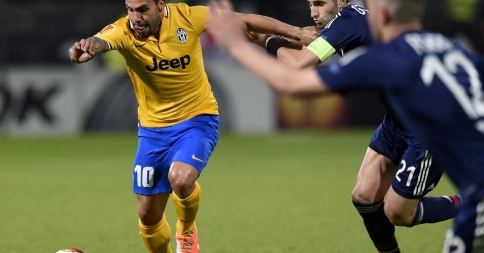 03.abr.2014 - Tevez, da Juventus, tenta se livrar de Jordan Ferri, do Lyon