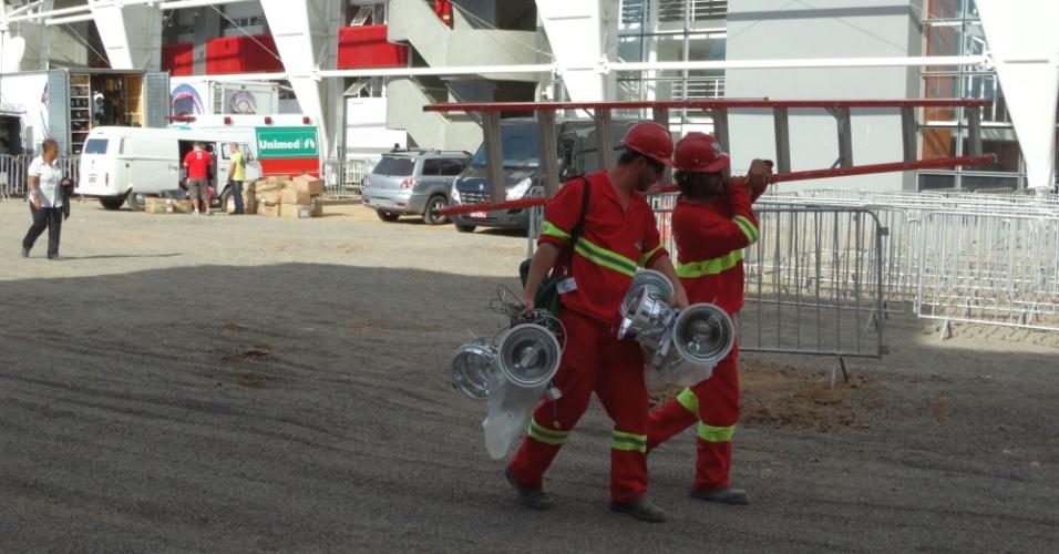 05 abr 2014 - Operários da Andrade Gutierrez carregam refletores após troca no Beira-Rio