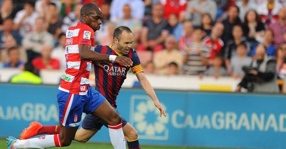 12.abr.2014 - Iniesta briga pela bola com Allan Nyom do Granada durante partida pelo Campeonato Espanhol