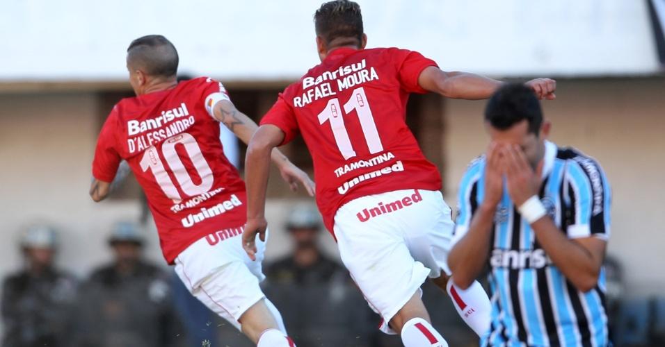 D'Alessandro e Rafael Moura comemoram gol do Inter na final do Campeonato Gaúcho, enquanto gremista lamenta goleada sofrida