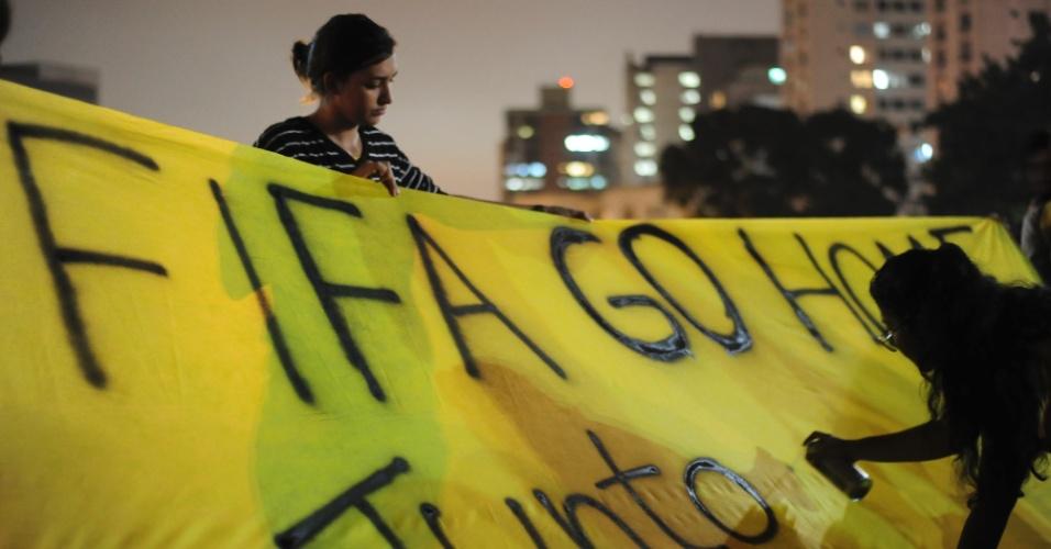 15.abr.2014 - Manifestantes escrevem faixa contra a Fifa durante ato contra a Copa do Mundo em São Paulo