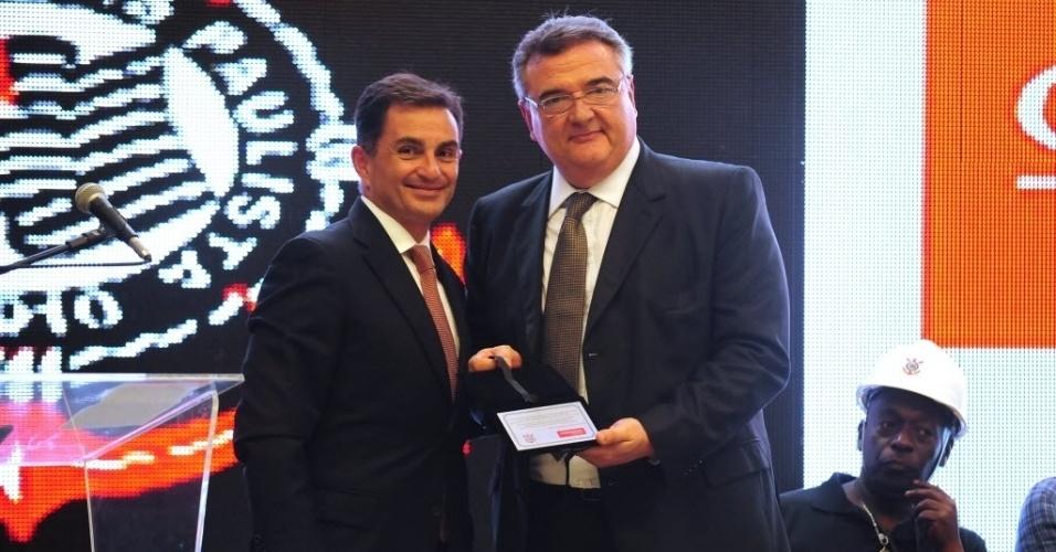 15.abr.2014 - Presidente do Corinthians, Mario Gobbi (dir.), recebe de representante da Odebrecht placa que simboliza a posse do Itaquerão. A partir de agora, então, o Corinthians é oficialmente o dono do estádio