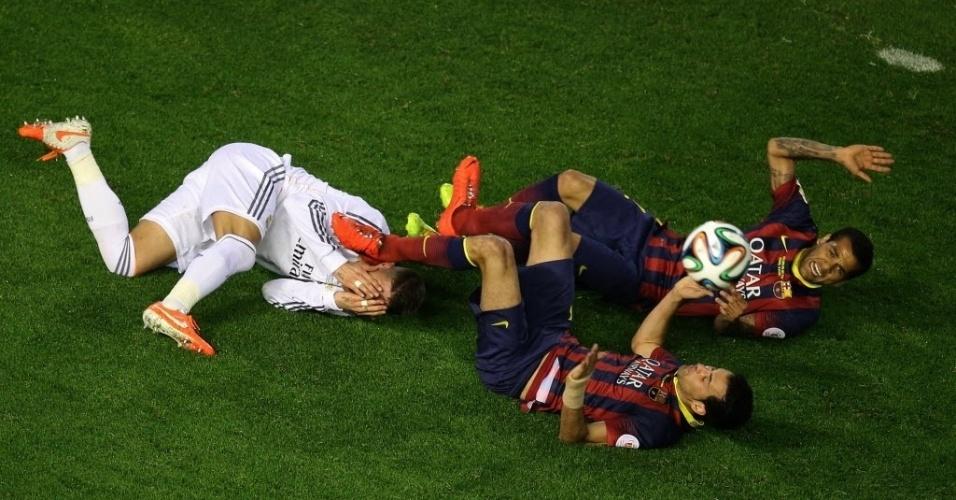 16.abr.2014 - Daniel Alves, Sergio Busquets e Sergio Ramos caem no gramado após choque em disputa de bola de cabeça na final da Copa do Rei