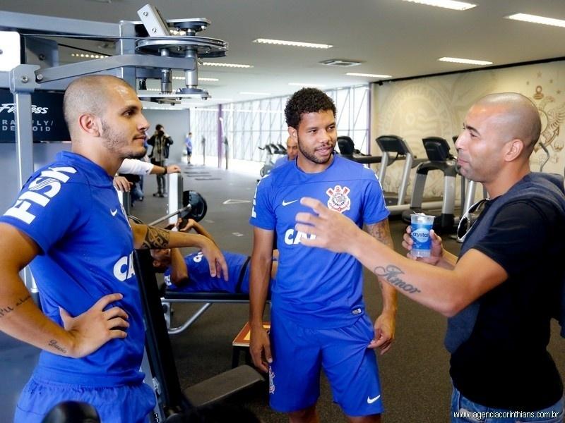 Emerson gesticula em conversa com Guilherme Andrade e Fábio Santos, em sua despedida do elenco do Corinthians; o atacante está de saída para o Botafogo
