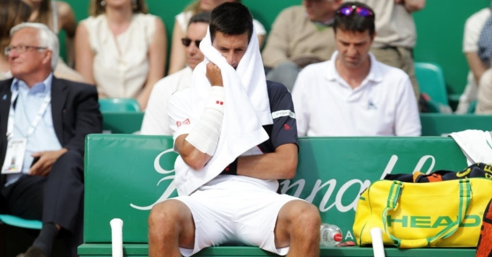 Novak Djokovic descansa durante intervalo da partida contra Roger Federer