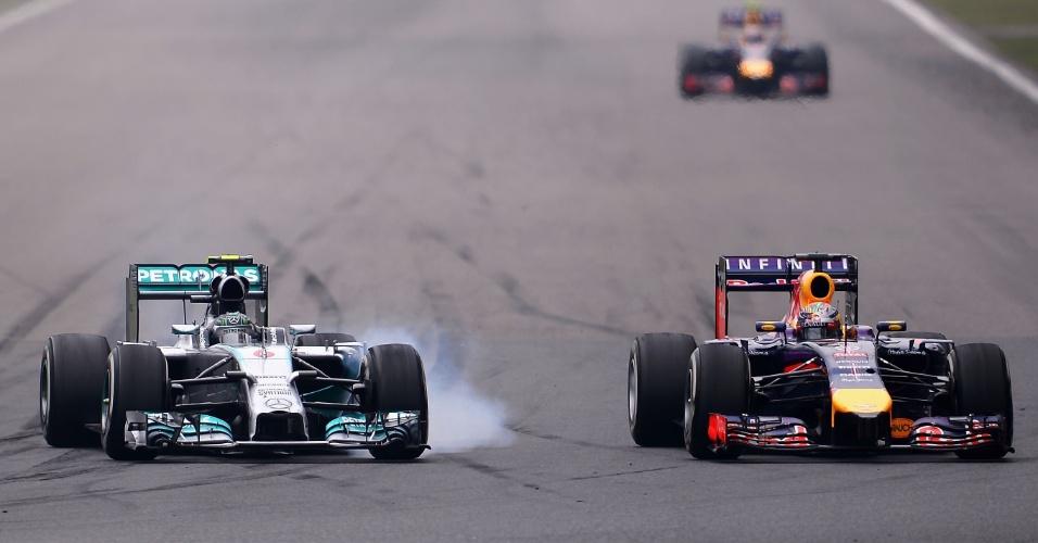20.abr.2014 - Nico Rosberg parte com tudo para ultrapassar Sebastian Vettel durante o GP da China