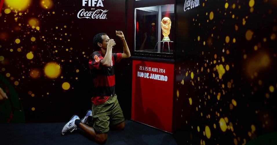 22.abr.2014 - Torcedor do Flamengo se ajoelha diante da Taça da Copa do Mundo durante evento realizado no estadio Maracanã, no Rio de Janeiro