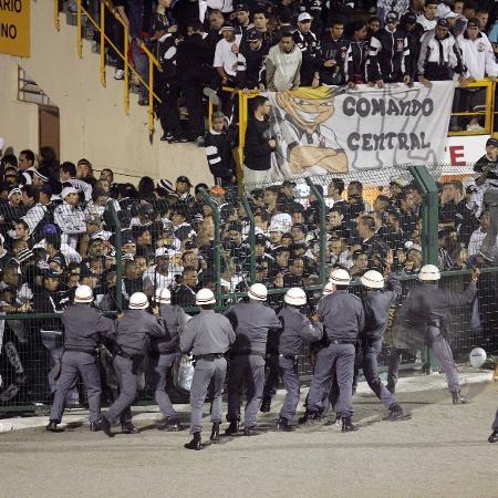 Policiais militares tentam conter a revolta da torcida do Corinthians após a eliminação diante do River Plate, pela Libertadores de 2006, no Pacaembu - Ayrton Vignola/Folha Imagem
