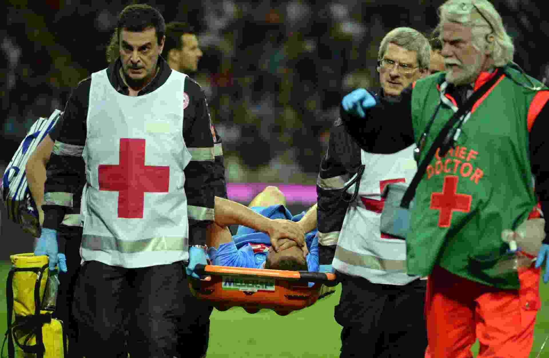 O atacante da seleção da Argentina e do Napoli, Gonzalo Gerardo Higuain, sai de campo na maca em jogo do Milan contra Napoli - OLIVIER MORIN/ AFP