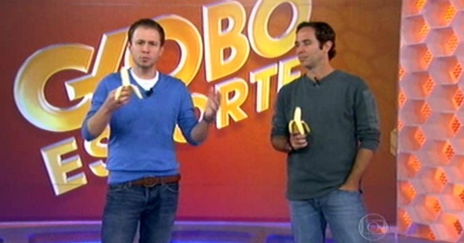 28.04.14 - Tiago Leifert e Caio Ribeiro comem banana em protesto contra racismo sofrido por Daniel Alves