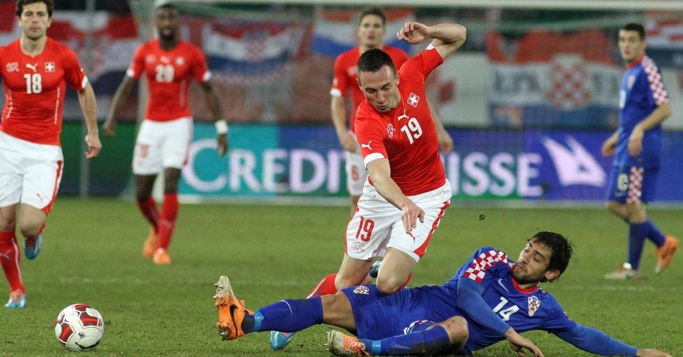 05.mar.2014 - Josip Drmic, da Suíça, perde a bola após carrinho de Mate Males, da Croácia, em amistoso disputado em St. Gallen