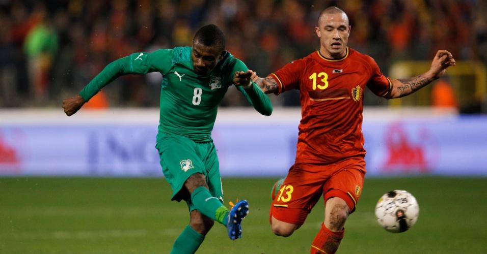 05.mar.2014 - Radja Nainggolan (d), da Bélgica, não evita o chute de Salomon Kalou, da Costa do Marfim, em amistoso disputado em Bruxelas