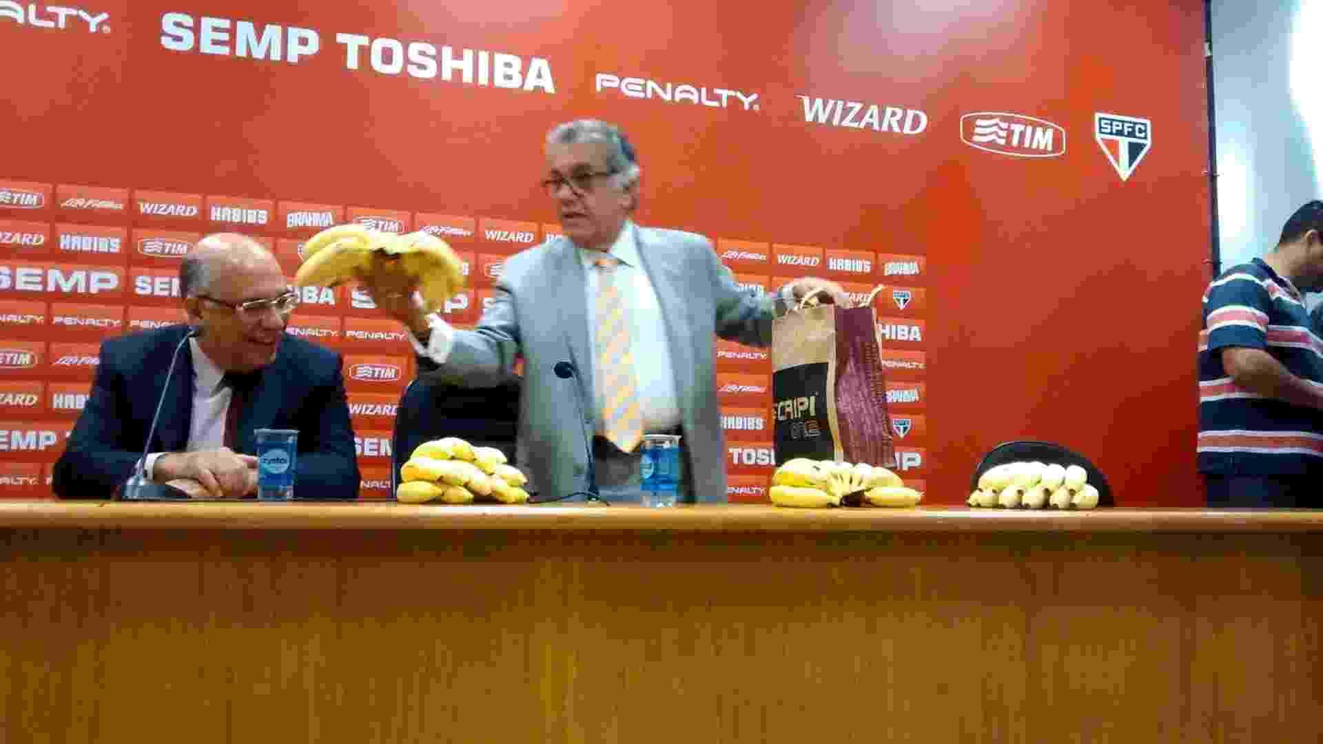 29.abr.2014 - Carlos Miguel Aidar, presidente do São Paulo, leva vários cachos de banana para a coletiva de imprensa como apoio a Daniel Alves após caso de racismo - Guilherme Palenzuela/UOL