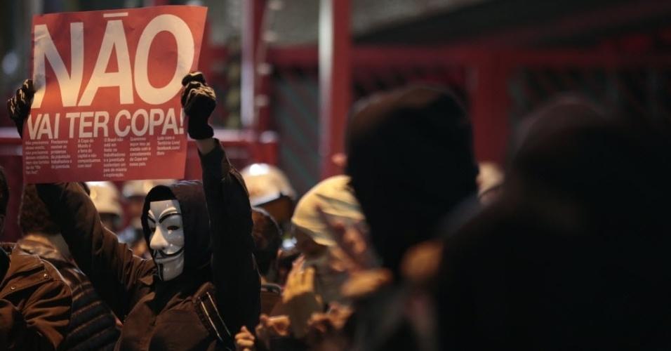 29.abr.2014 - Manifestante mascarado ergue cartaz contra a realização da Copa do Mundo no Brasil em ato na região do Tatuapé, em São Paulo