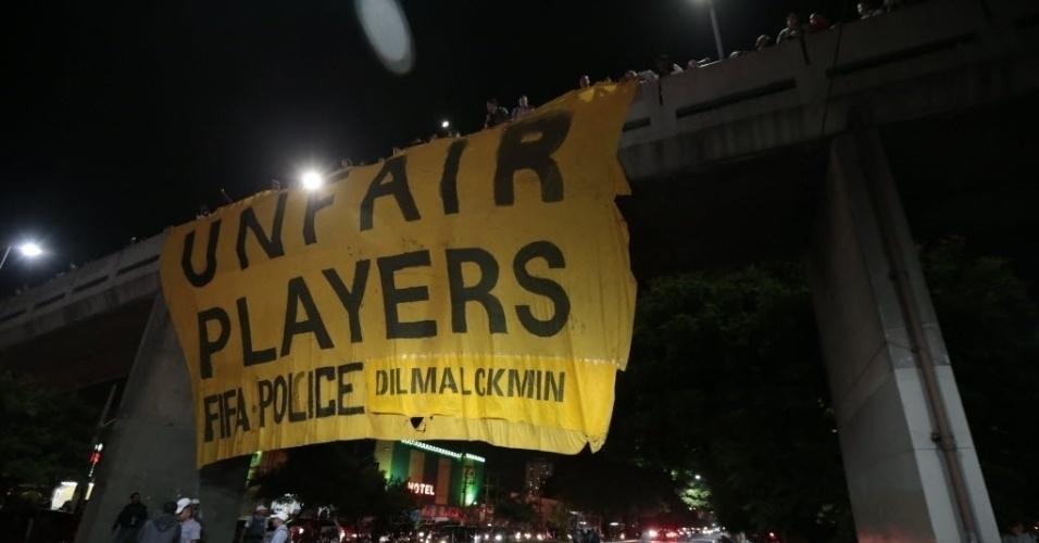 """29.abr.2014 - Manifestantes estendem faixa na ponte estaiada sobre a Avenida Sarim Farah Maluf, na zona lesta de São Paulo. Em inglês, bandeira diz que Fifa, polícia, Dilma e Alckmin são """"jogadores injustos"""""""
