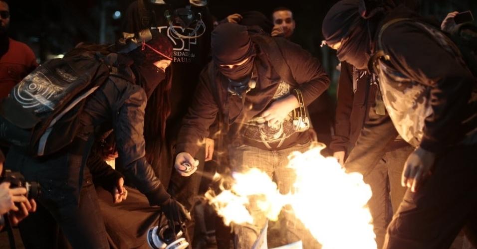 29.abr.2014 - Manifestantes queimam álbum de figurinhas em protesto contra a Copa do Mundo no bairro do Tatuapé, em São Paulo
