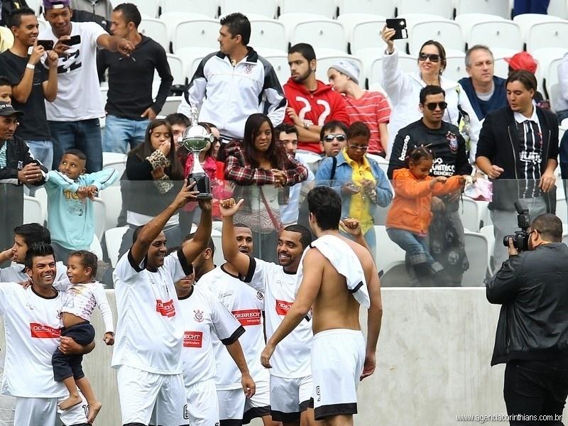 01.ami.2014 - Funcionários do Itaquerão levantam taça simbólica após jogo teste do estádio