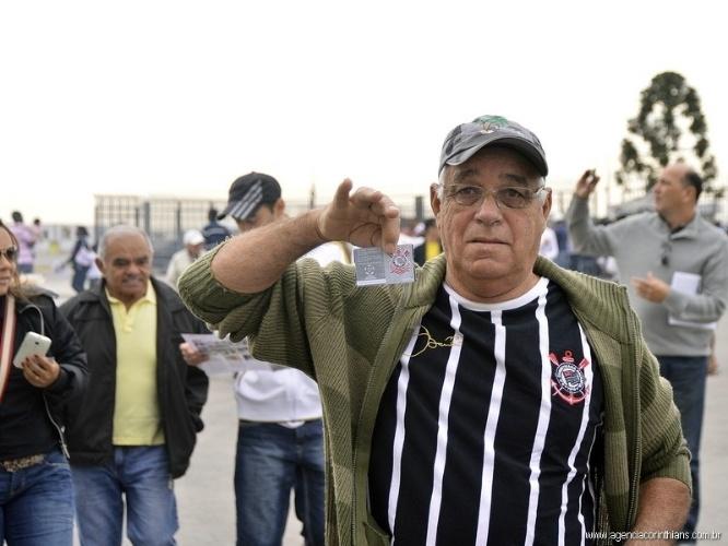 01.mai.2014 - Torcedor exibe ingresso para ver o jogo teste do Itaquerão, com funcionários da Odebrecht