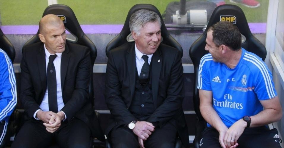 07.mai.2014 - Ao lado do ex-jogador Zidane, técnico do Real Madrid, Carlo Ancelotti, conversa com seu auxiliar técnico durante a partida contra o Valladolid