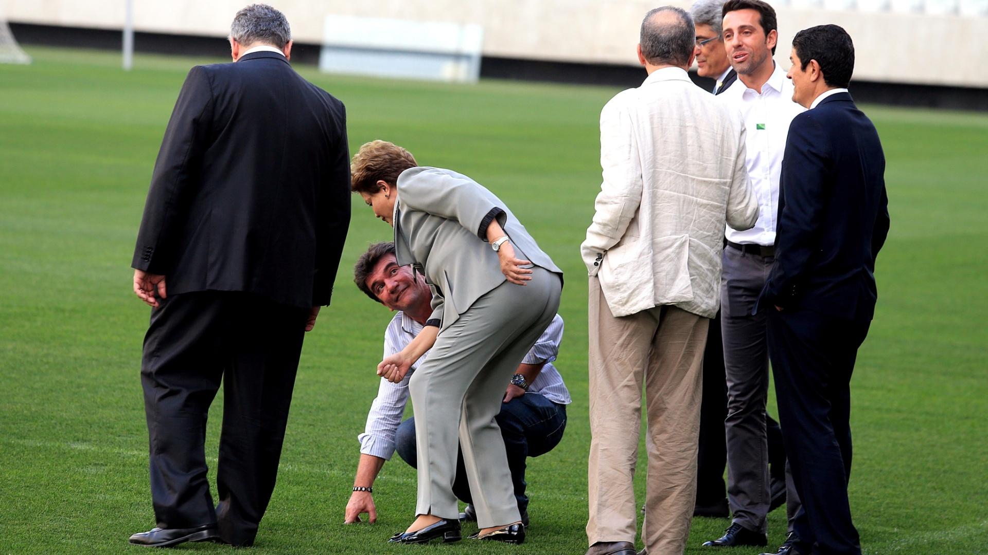 08.05.14 - Andrés Sanchez apresenta o gramado do Itaquerão à Dilma; presidente chegou a se desequilibrar quando se abaixou, mas foi auxiliada por Sanchez e Alexandre Padilha