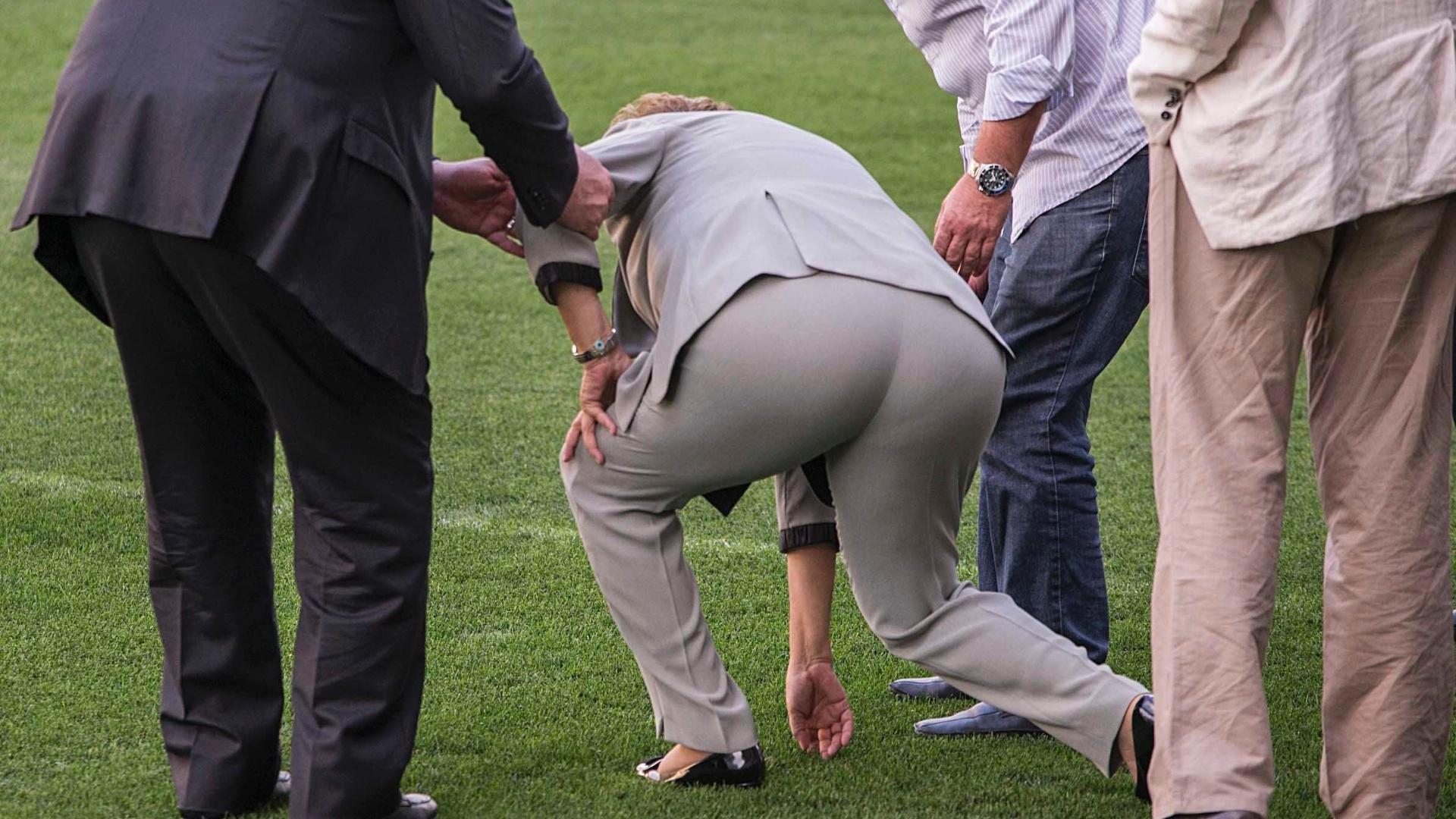 08.05.14 - Dilma Rousseff toca no gramado do Itaquerão, estádio de abertura da Copa do Mundo; presidente chegou a se desequilibrar quando se abaixou, mas foi auxiliada por Andrés Sanchez e Alexandre Padilha