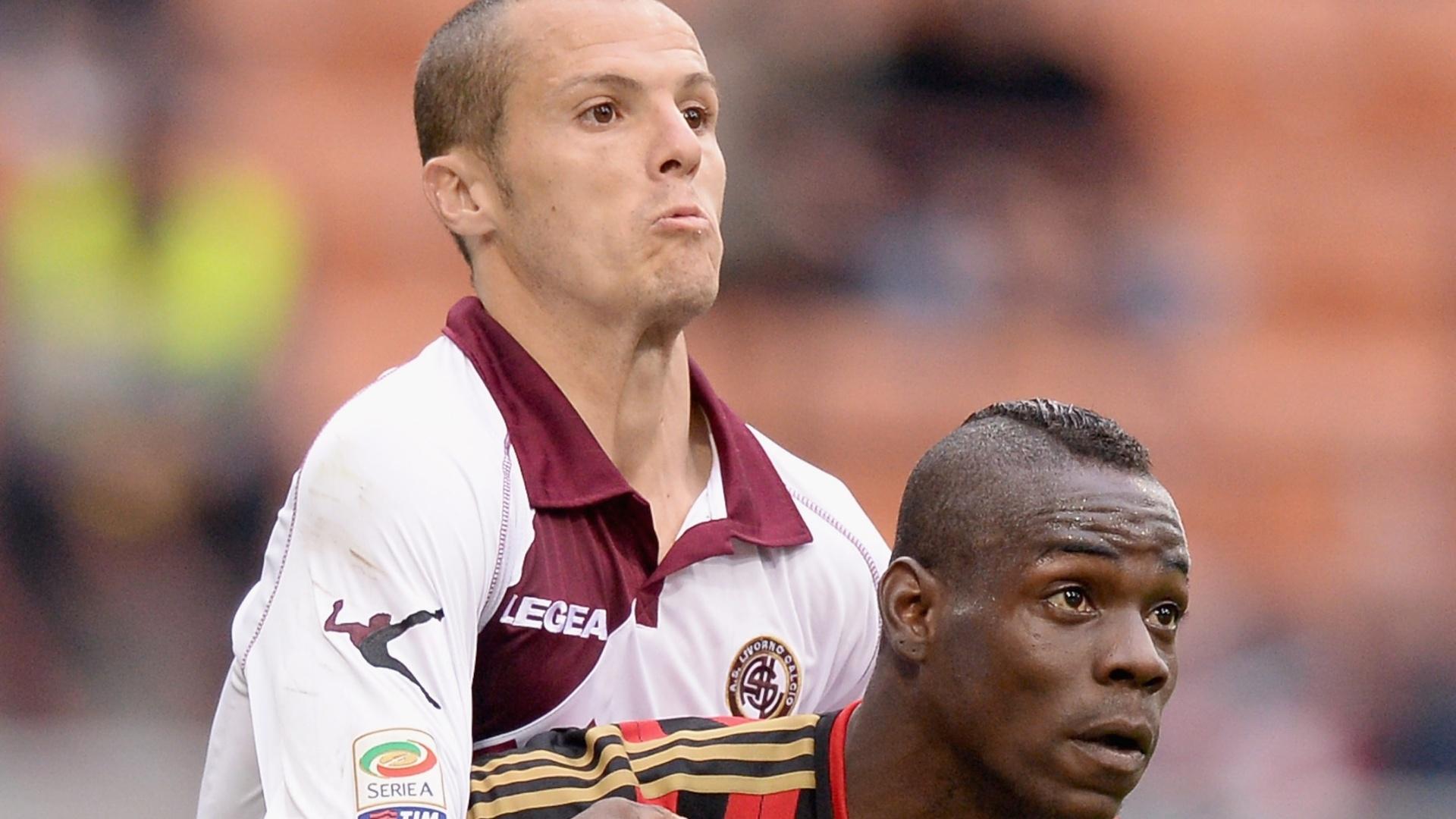 19.abr.2014 - Djamel Mesbah (e), do Livorno, faz marcação cerrada em Mario Balotelli, do Milan, durante partida do Campeonato Italiano