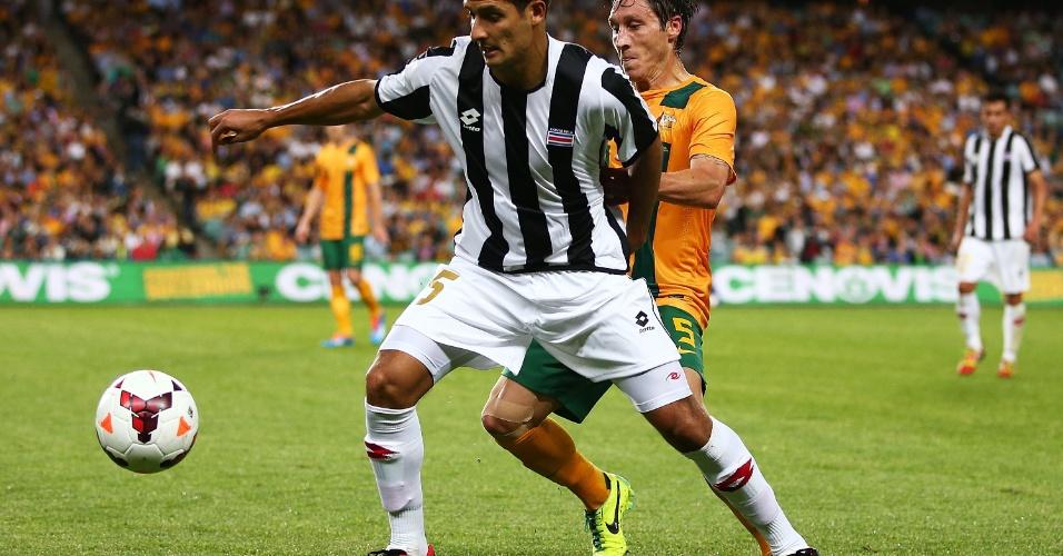 19.nov.2013 - Celso Borges (à frente), da Costa Rica, leva a melhor sobre o australiano Mark Milligan em amistoso disputado em Sydney