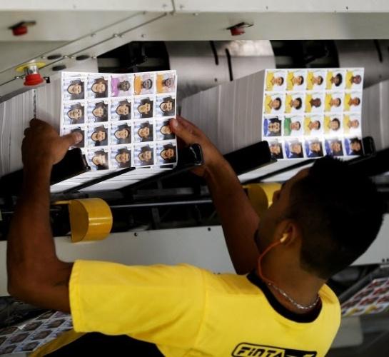 Máquinas e funcionários dividem as etapas de fabricação das figurinhas da Copa do Mundo na fábrica da Panini, em Barueri