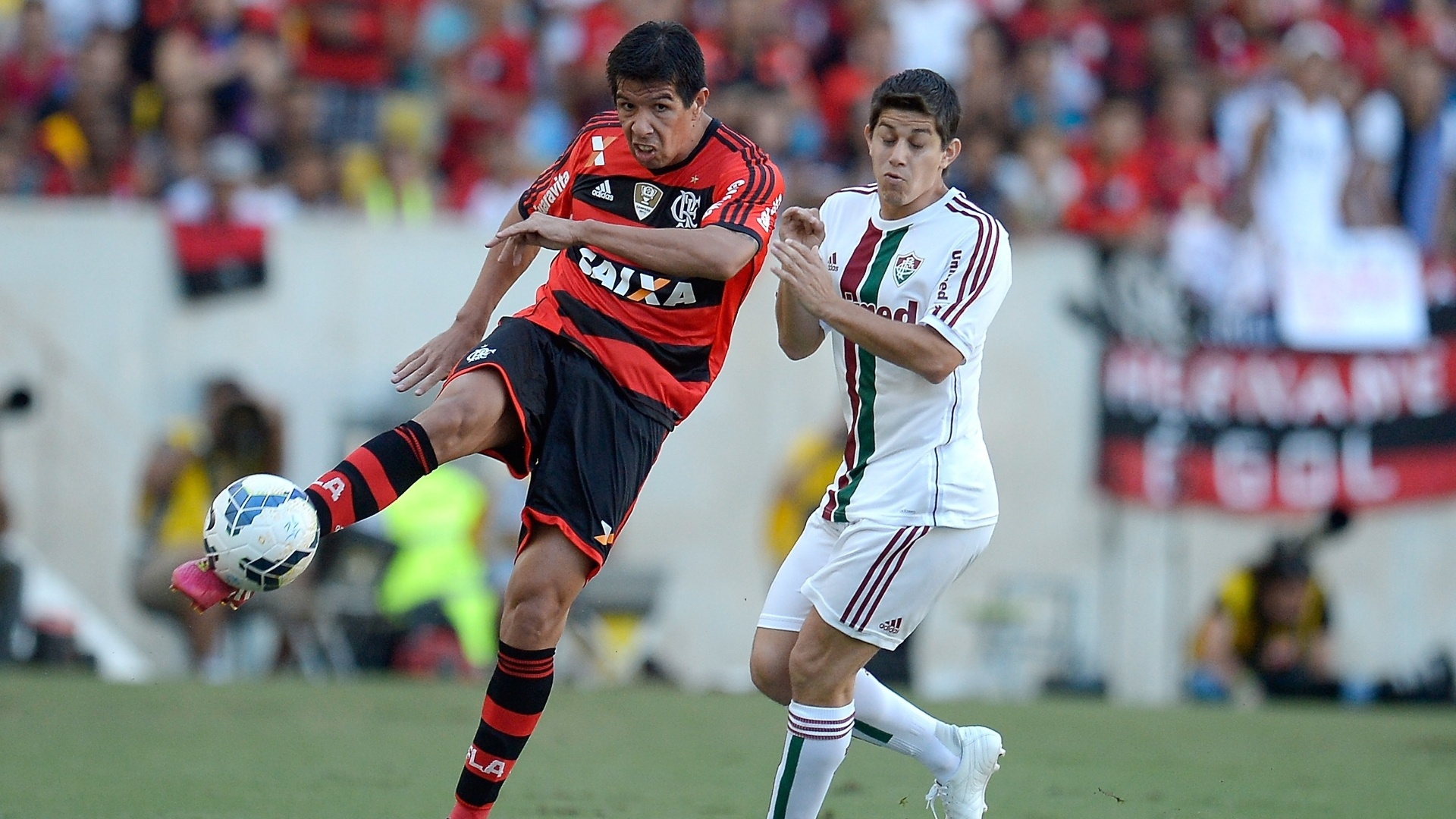 Victor Cáceres, do Flamengo, arrisca chute enquanto é combatido por Conca, do Fluminense - 11.05.14