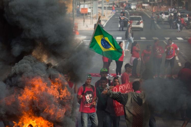 15.mai.2014 - Jovens manifestantes próximos de pneus queimados perto da Arena Corinthians, em Itaquera, palco da abertura da Copa de 2014