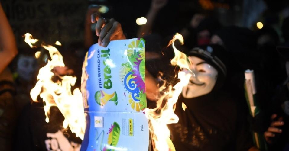 15.mai.2014 - Manifestante queima álbum da Copa durante protesto no Rio de Janeiro contra o Mundial