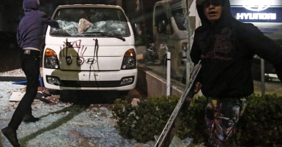 Manifestante lança pedra num carro em concessionária em São Paulo