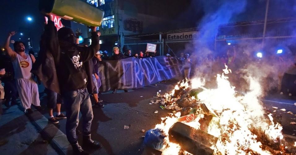 Manifestante mascarado joga lixeira em fogueira na rua, em São Paulo