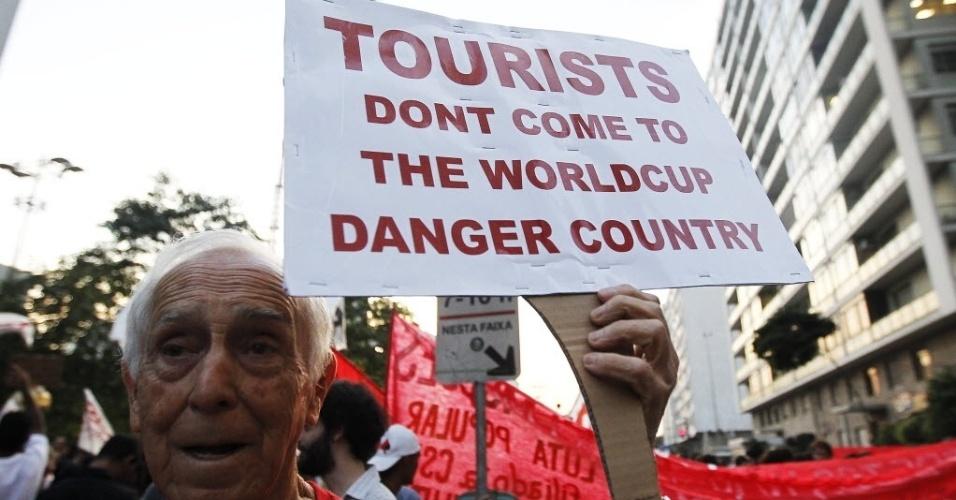 """Manifestante usa cartaz em inglês para pedir que os turistas não venham ao Brasil por ser um """"país perigoso"""""""