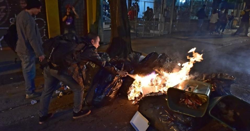 Manifestante usa spray para espalhar fogo em amontoado de sacos de lixo